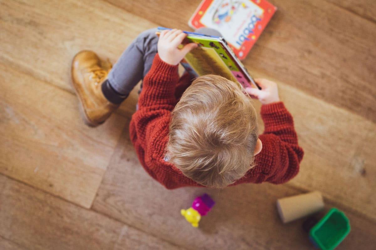 Junge sitzt mit Bildbuch in der Hand auf dem Boden.