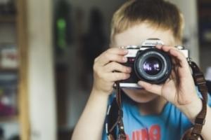 Kind hält Kamera mit Objektiv vor das Gesicht