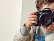 Ein Kind hält eine Kamera in den Händen. Der Umgang mit Fotos in der Kita sollte mit Eltern und im Team thematisiert werden.